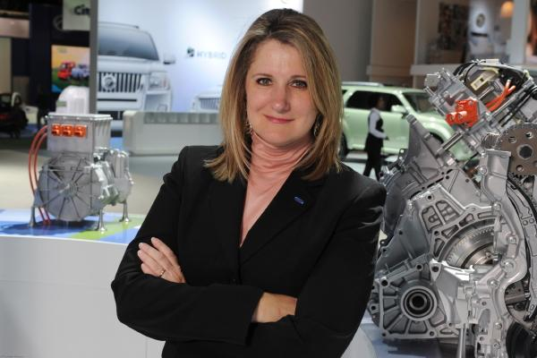 Professional Women in Automotive industry standing in from on Engine